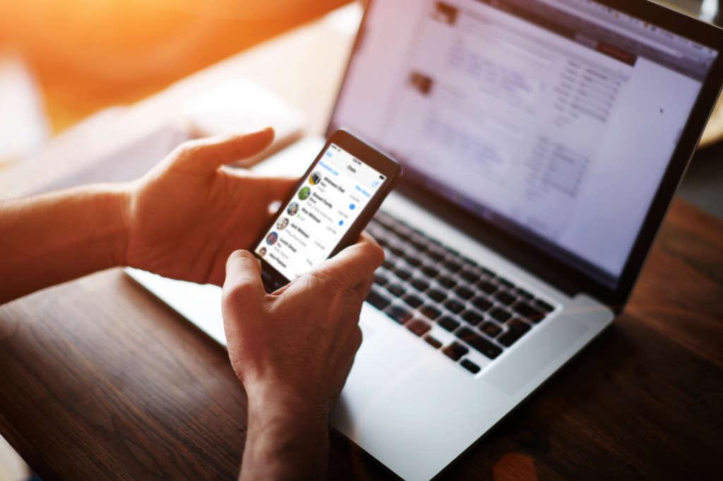 Смартфон в руках и ноутбук на столе