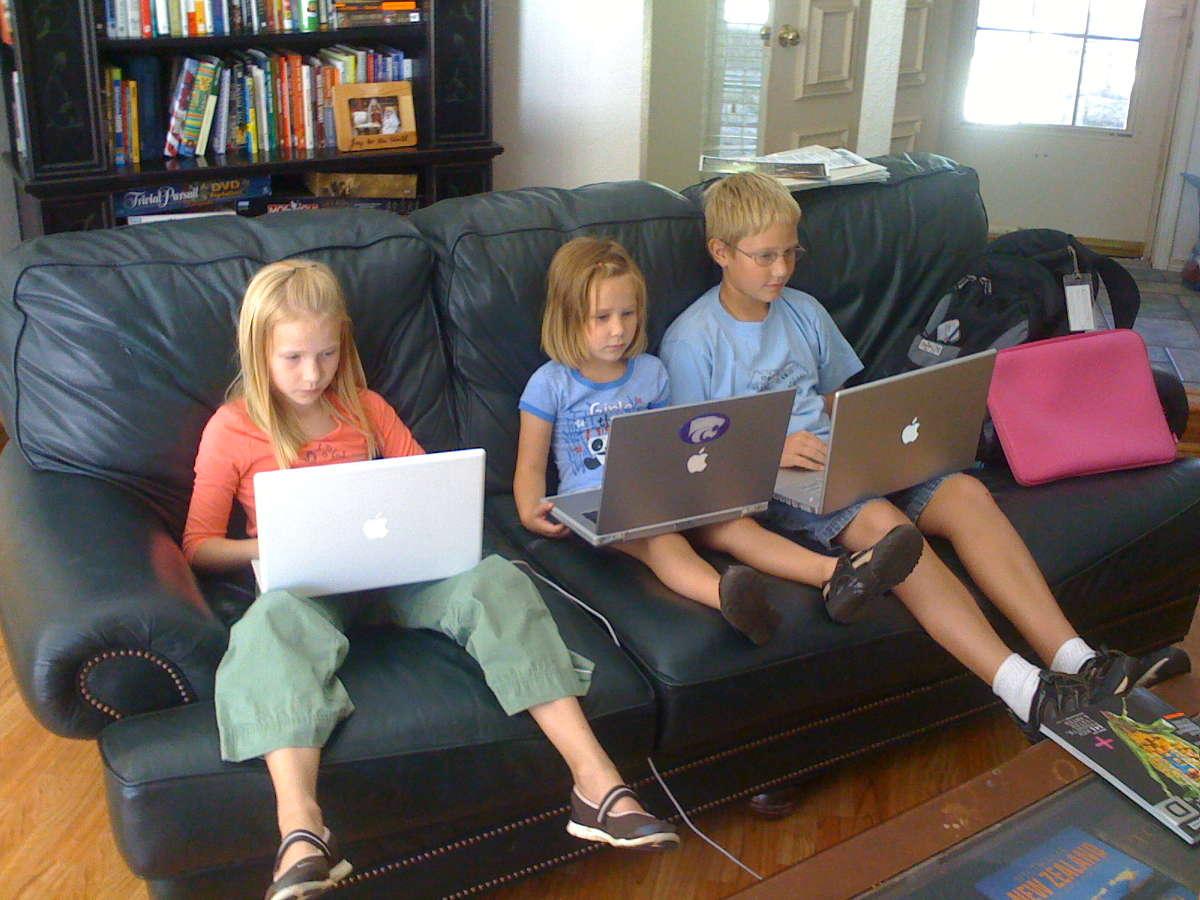 Дети с ноутбуками на диване