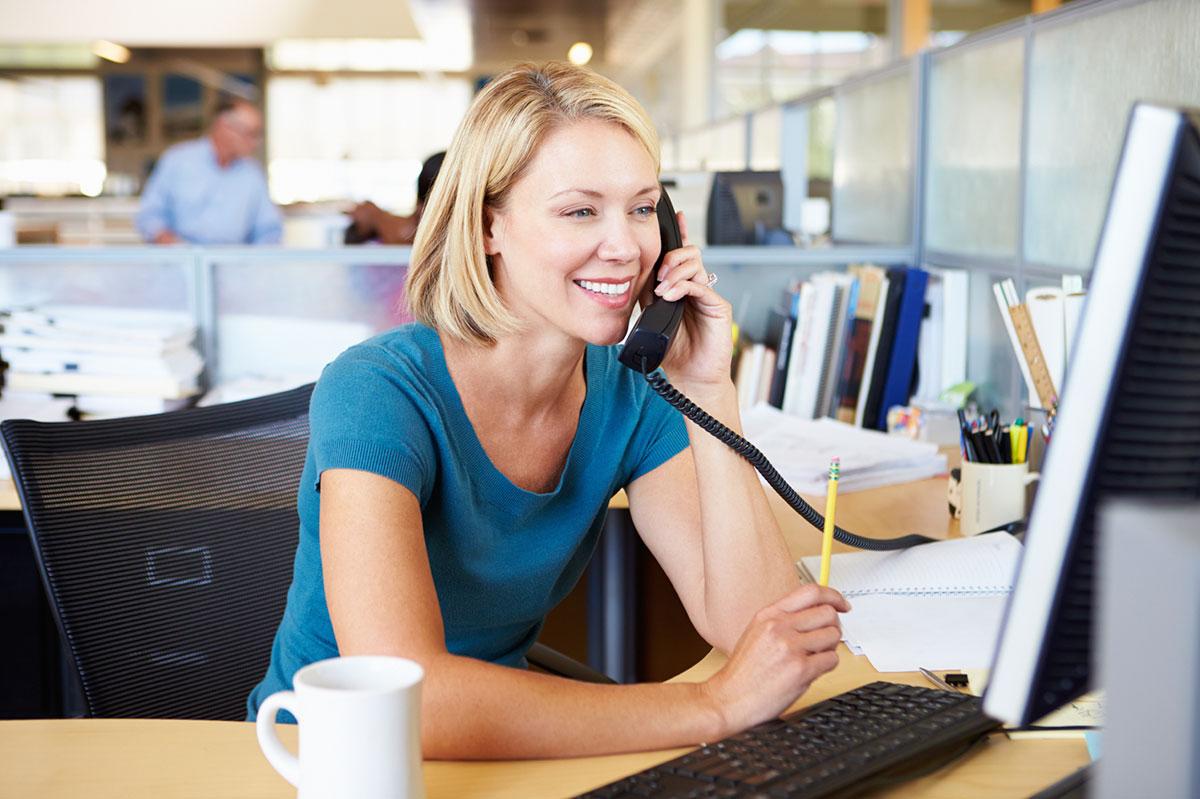 Девушка в офисе говорит по телефону