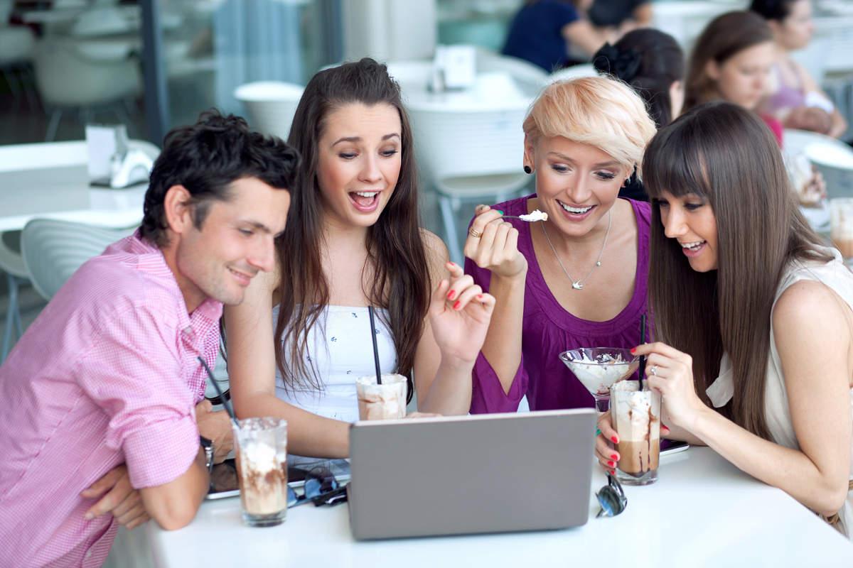 Люди в кафе перед компьютером