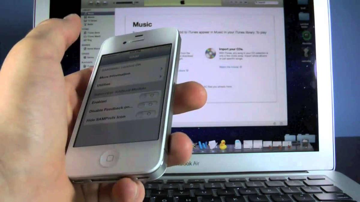 Смартфон в руке на фоне компьютера