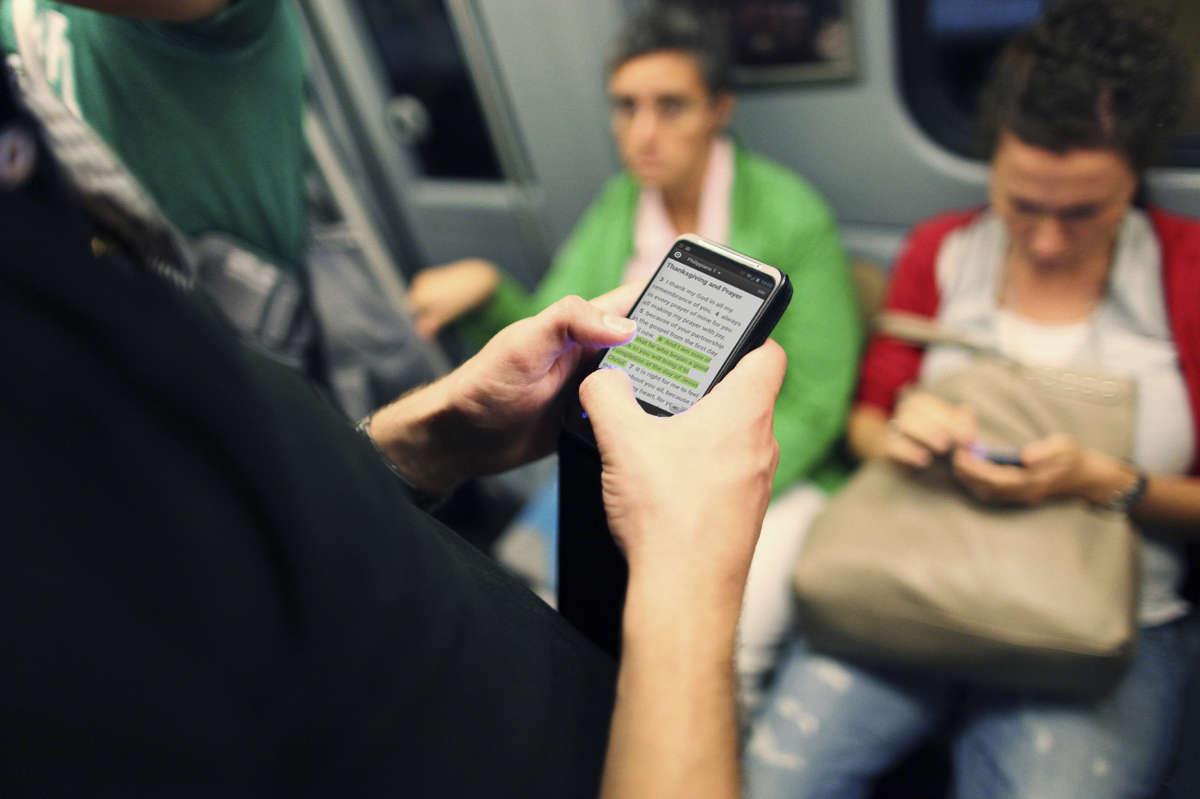 Люди с телефонами в метро
