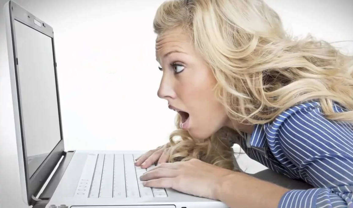 Удивлённая девушка смотрит на экран