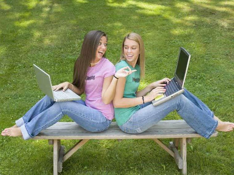 Две девушки с ноутбуками в парке