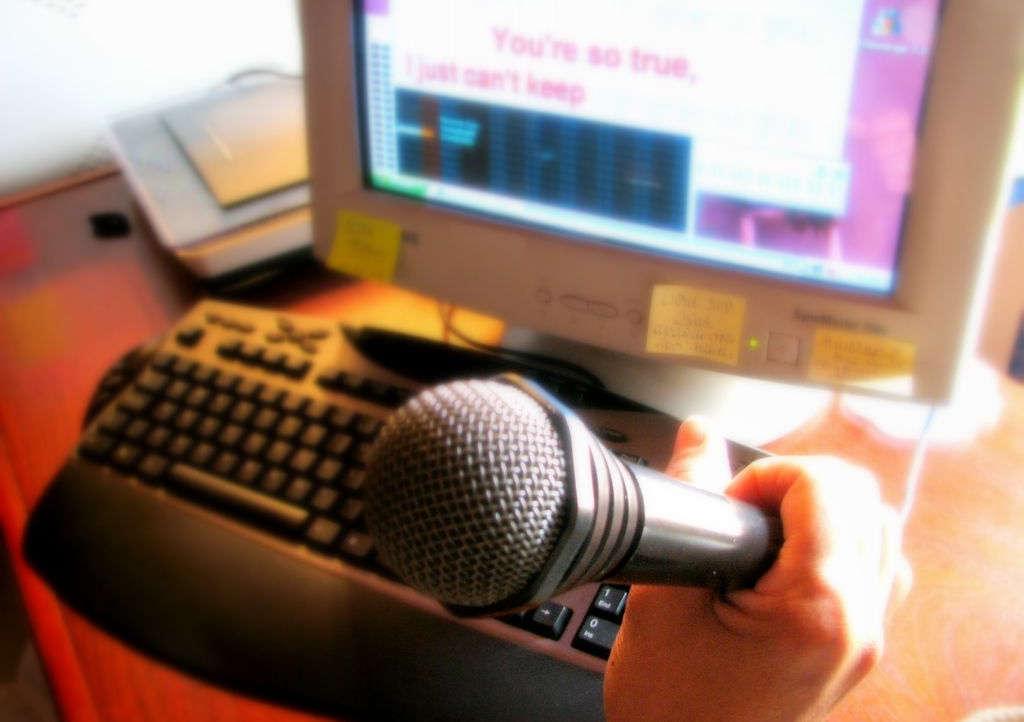 Микрофон в руке и компьютер
