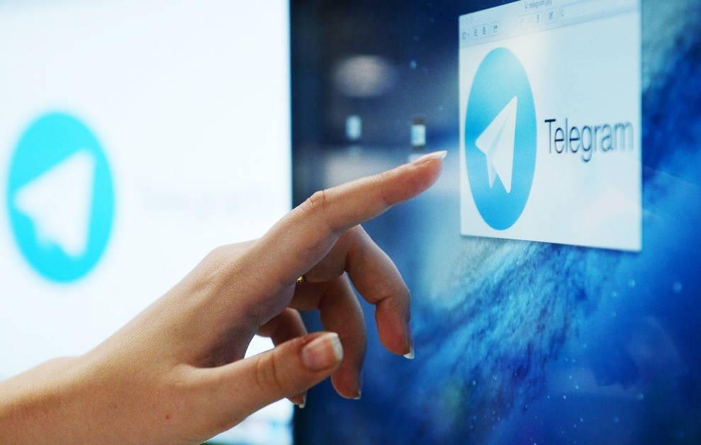 Рука указывает на экран с логотипом Telegram